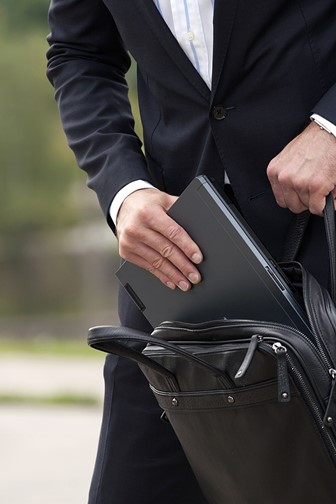 businessperson placing a laptop computer into a leather laptop case
